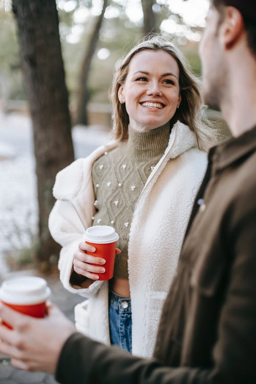 Young cheerful couple having hot drinks in paper cups while talking on street looking at each other