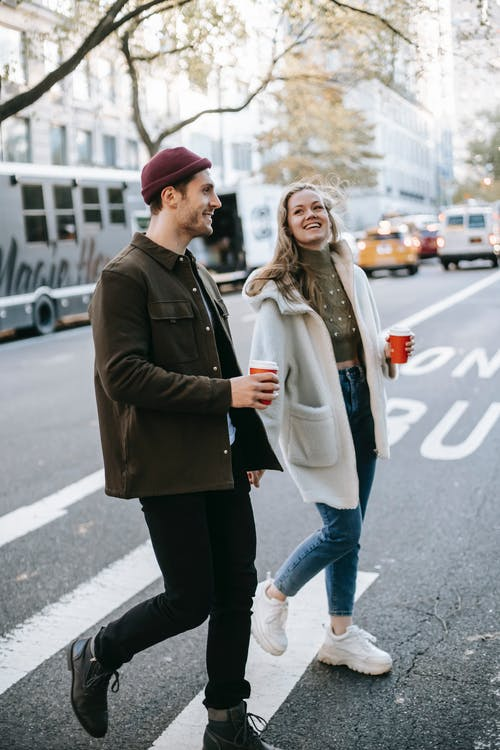 Young smiling couple in warm clothes strolling on city street with paper cups with drink and talking in daylight