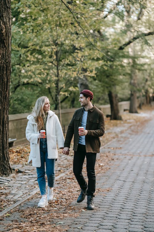Young couple strolling and chatting in park with coffee cups