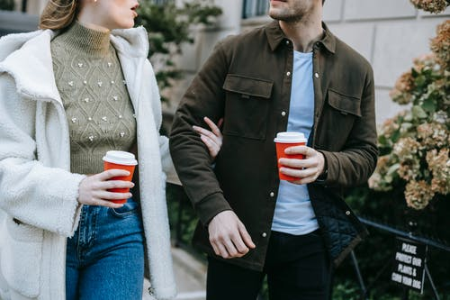 Crop anonymous young couple in stylish clothes drinking takeaway coffee and talking while walking together in city street during weekend