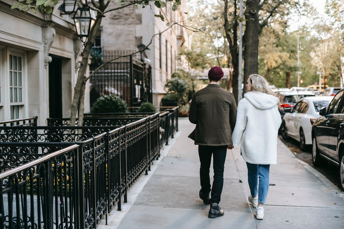 Stylish young couple walking in city residential district