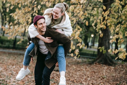 Happy young guy in trendy outfit smiling while giving piggyback ride to expressive girlfriend with having fun together in autumn park