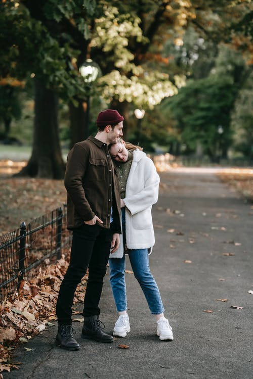 Full body of happy romantic young couple in stylish outfits embracing while standing on narrow alley in autumn park