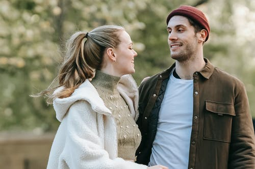 Smiling young couple standing in park during romantic date