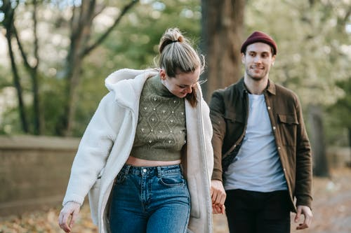 Cheerful young stylish lady in warm clothes holding hand of smiling boyfriend while walking together in park on sunny autumn day