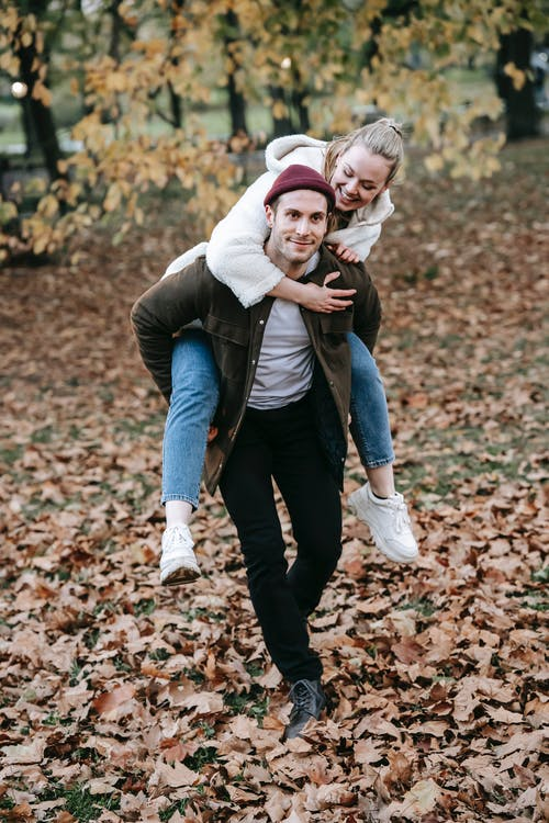 Romantic young male giving piggyback ride to happy girlfriend in nature