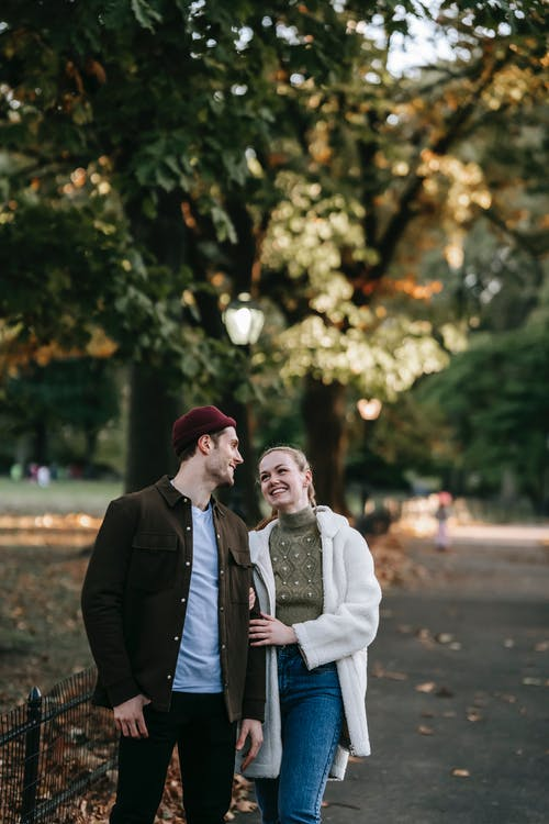 Happy young male and female millennials in stylish outfits smiling and looking at each other during romantic date in autumn park on sunny day