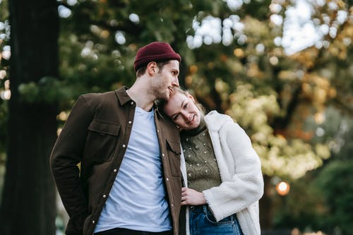 Happy loving young couple in stylish clothes cuddling while standing in park during romantic date on sunny autumn day