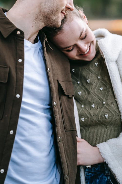 Happy young woman in trendy warm outfit cuddling crop boyfriend and smiling while spending time together in park on sunny day