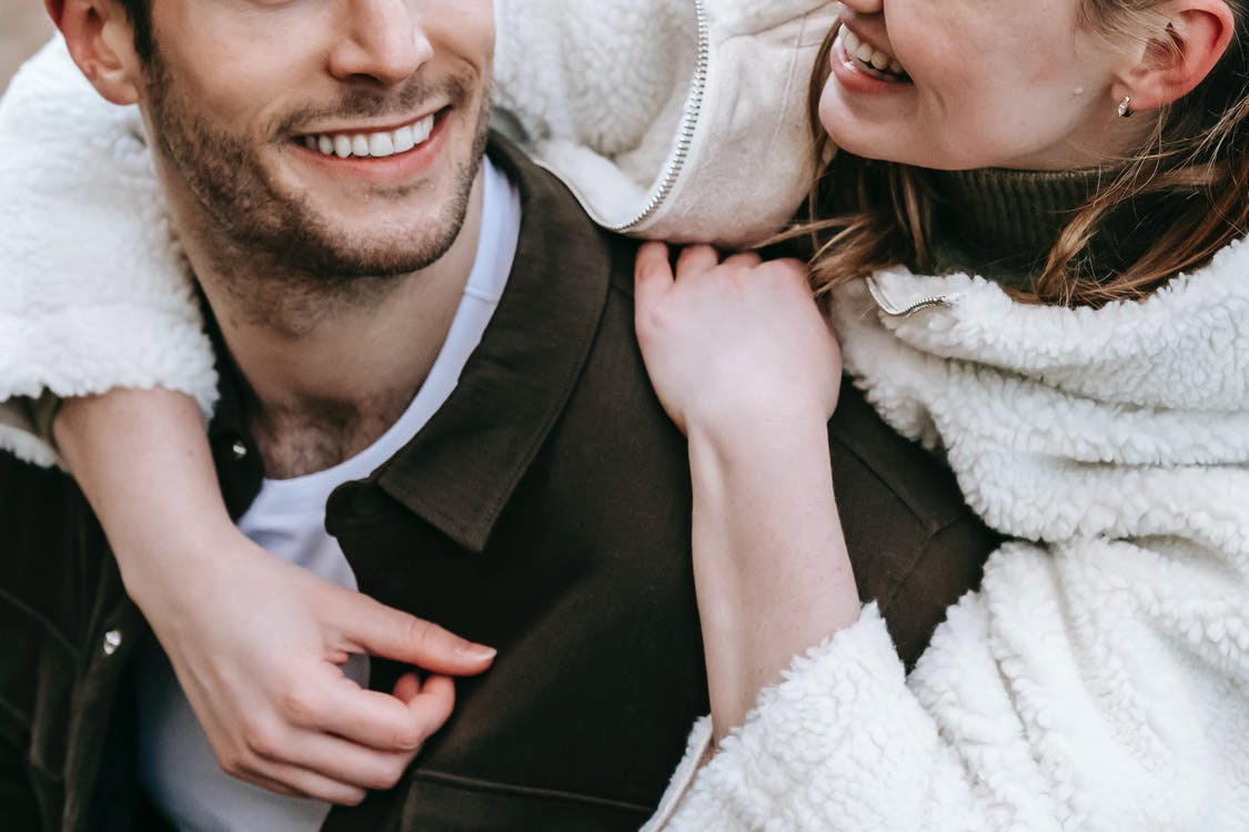 Crop anonymous couple in warm casual clothes cuddling each other and smiling together