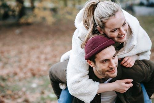 Delighted boyfriend giving piggyback ride to beloved girlfriend