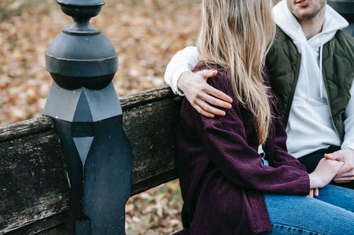 Young couple in stylish warm clothes embracing near fence