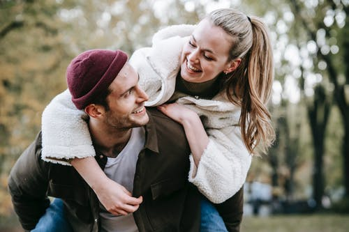 Joyful girlfriend embracing smiling boyfriend in hat