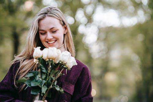 Wanita Dengan Cardigan Ungu Memegang Bunga Putih