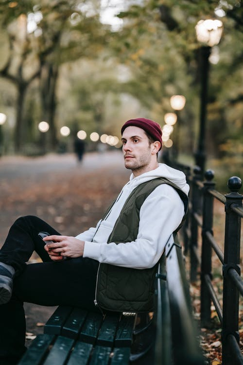 Side view of calm young male with beard in casual outfit sitting on bench in park and looking away while chatting on smartphone