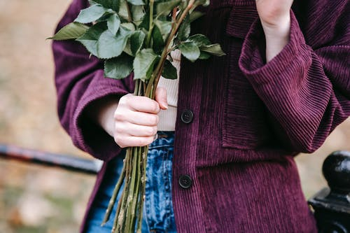 Crop anonymous young female in jeans and warm jacket standing in park with bouquet of flowers leaning on metal fence