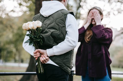 Crop unrecognizable man in warm clothes going to give bouquet of roses as surprise gift to happy girlfriend covering eyes with hands in park