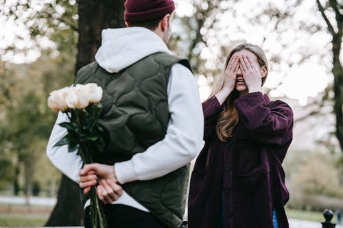 Man giving flowers as present to girlfriend