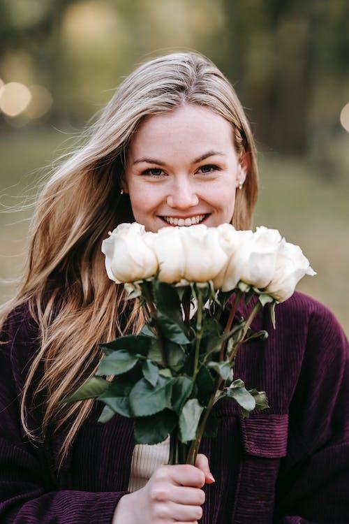 Wanita Dengan Kemeja Lengan Panjang Maroon Memegang Bunga Putih