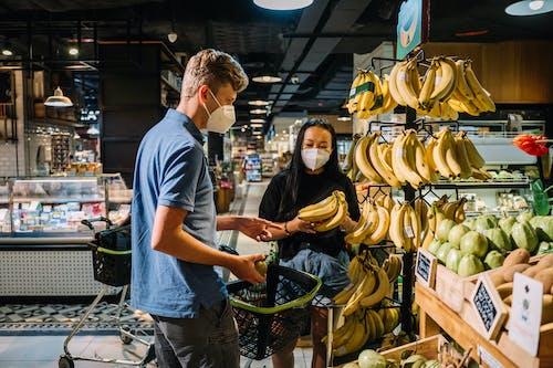 Couple Wearing Face Masks Buying Fresh Bananas
