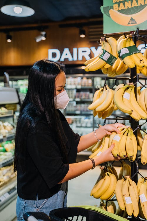 Woman With Face Mask Holding Yellow Bananas