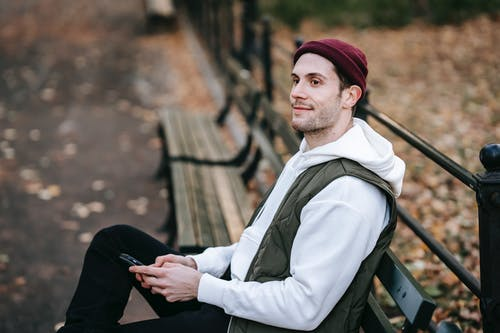 From above of content young male with beard sitting on bench in park and looking away while text messaging on smartphone
