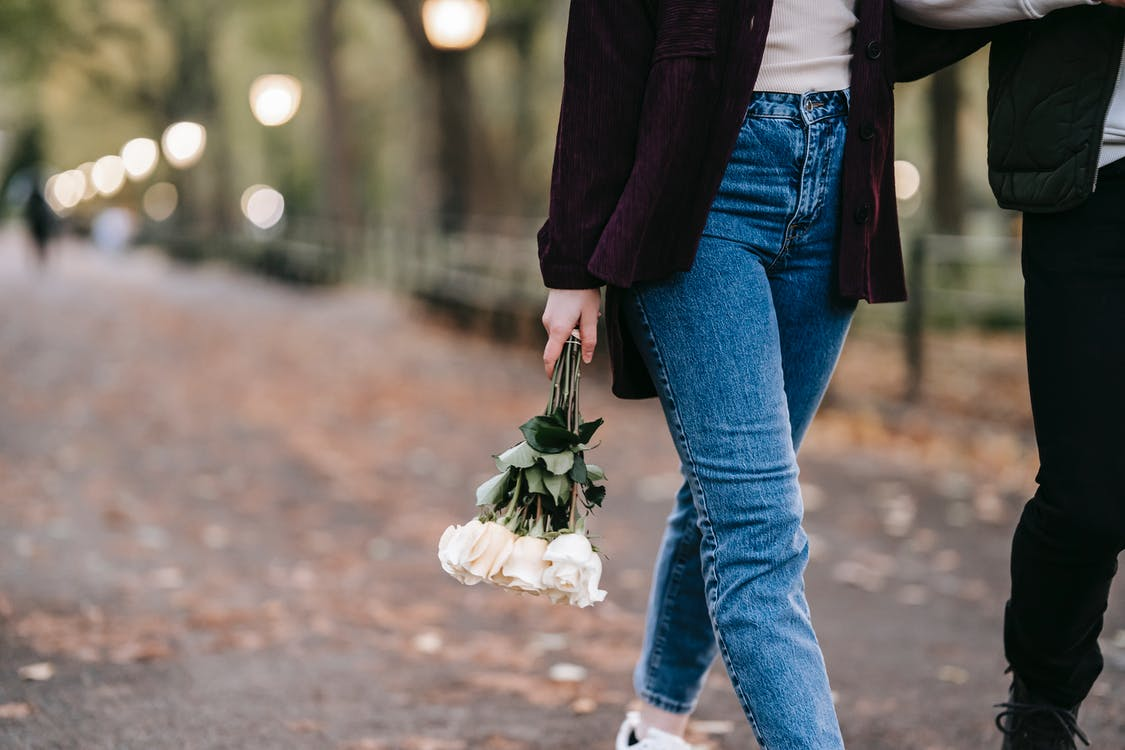 Crop anonymous female in jeans with bouquet of fresh white roses walking in park on blurred background