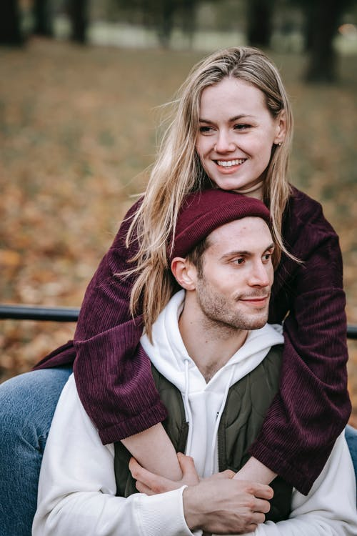 Smiling girlfriend embracing male partner in park