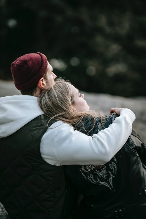 Back view of man in casual clothes embracing dreamy female partner while looking away on blurred background