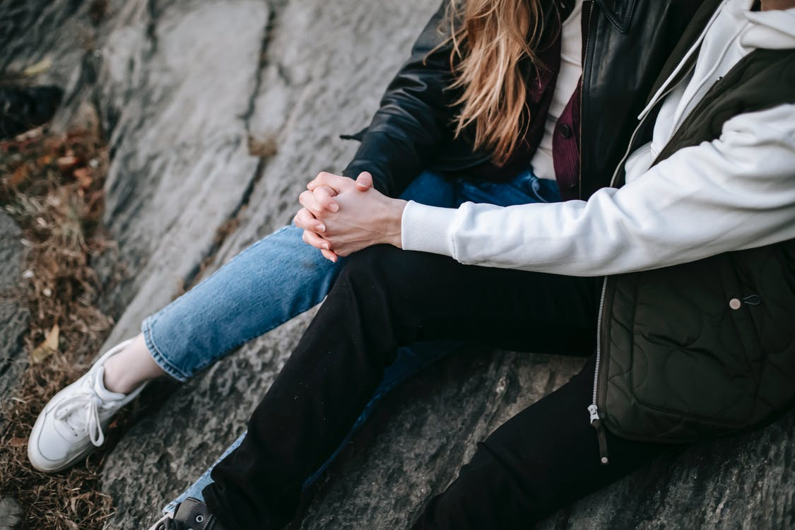 Женщина в черной куртке и синих джинсовых джинсах сидит на серой скале