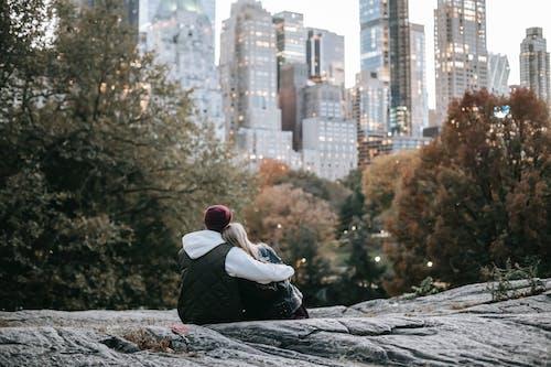 Romantic anonymous couple sitting on stony ground in city