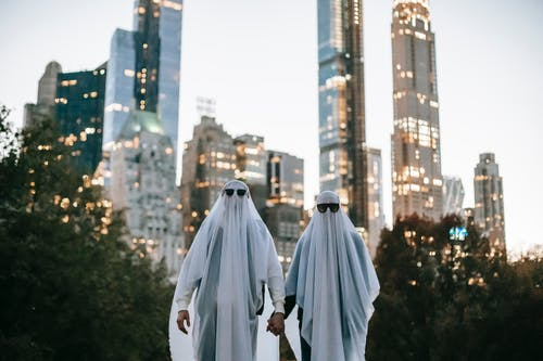 Unrecognizable couple in ghost costume on street