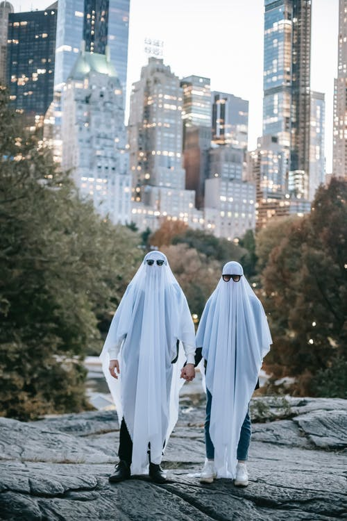 Full body of anonymous couple wearing spooky ghost costumes and sunglasses holding hands while standing on rocky ground in park with green trees and modern illuminated buildings during Halloween