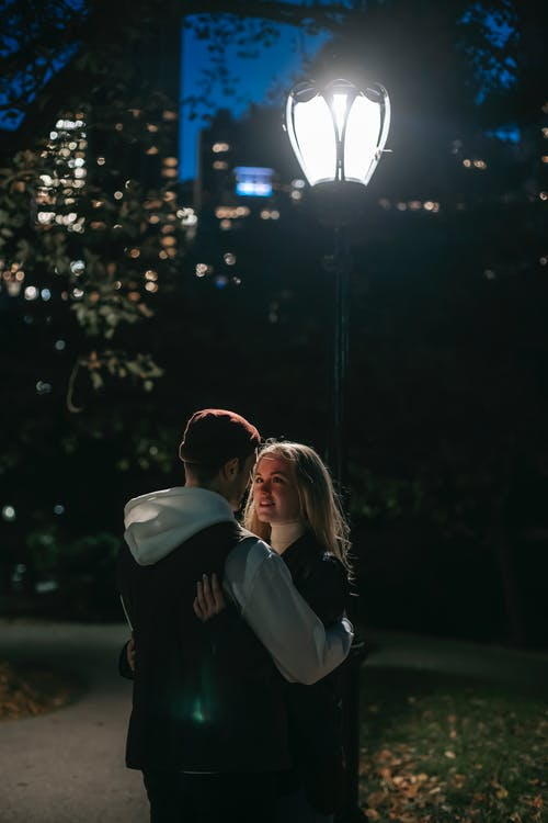 Romantic couple hugging in park at night