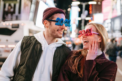 Smiling couple wearing decorated 2021 glasses looking at each other while standing on street with illuminated buildings on blurred background