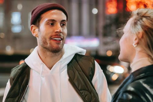 Cheerful man with anonymous woman on street