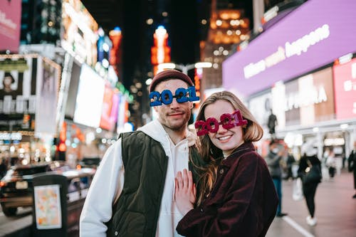 Cheerful couple wearing decorated 2021 glasses looking at camera and embracing while standing on square with glowing modern buildings on blurred background at night time