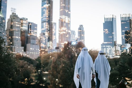 Unrecognizable couple in ghost costumes in city