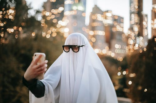 Anonymous person wearing ghost costume and sunglasses taking self portrait on smartphone while standing on street with trees and skyscrapers on blurred background during Halloween
