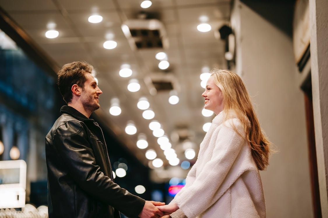 Мужчина в черной кожаной куртке стоит рядом с женщиной в белом пальто
