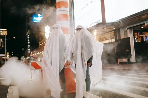 Full body of anonymous couple wearing ghost costumes and sunglasses holding hands while standing on crosswalk near steam pipe at night time