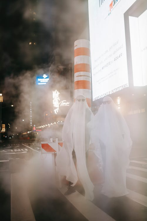 Full body of anonymous couple wearing ghost costumes and sunglasses standing on crosswalk with steam pipe at night city with glowing signboards during Halloween