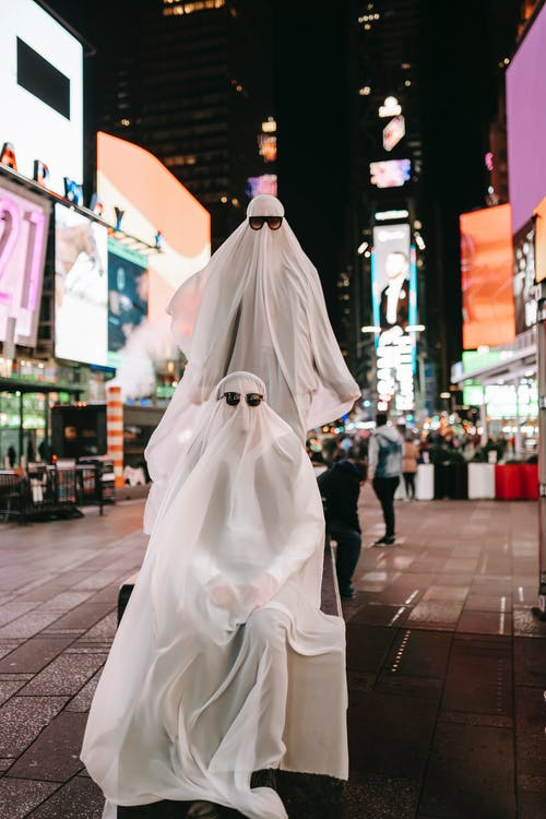 Full body of anonymous couple wearing ghost costumes and sunglasses on stand in night street with glowing signboard on buildings during Halloween