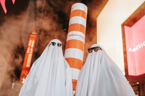 Unrecognizable couple in ghost costumes on night street with buildings