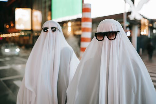Anonymous couple wearing ghost costumes and sunglasses standing on road near steam pipe and glowing signboards on blurred background on street