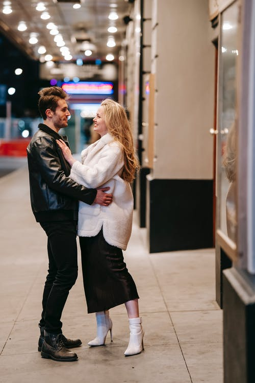 Side view full body of romantic couple looking at each other and embracing while standing in subway hall during date on evening time