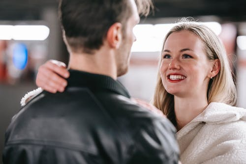 Crop cheerful couple hugging tenderly while toothy smiling and looking at each other