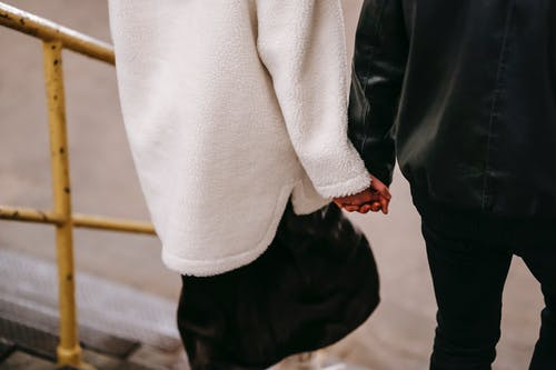 Crop anonymous couple in warm clothes holding hands while going downstairs in city