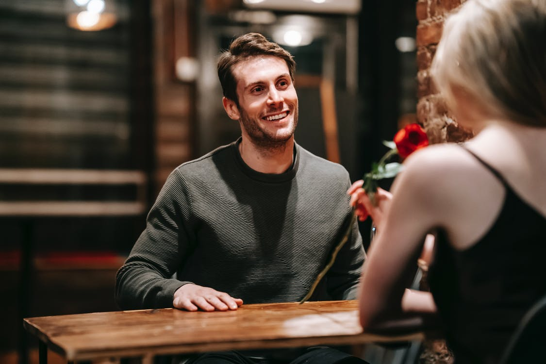 Happy couple sitting at table in cafe during date