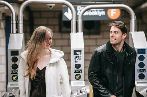 Young smiling couple in warm outwear strolling through metal turnstile in light modern subway